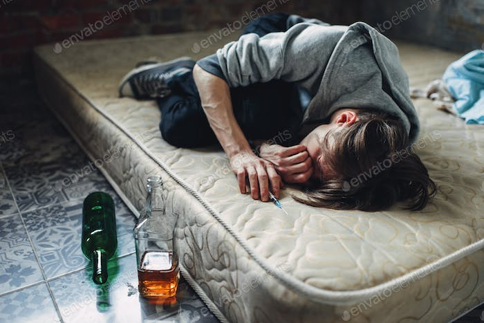 Druggy sleeping, bottle of alcohol is near