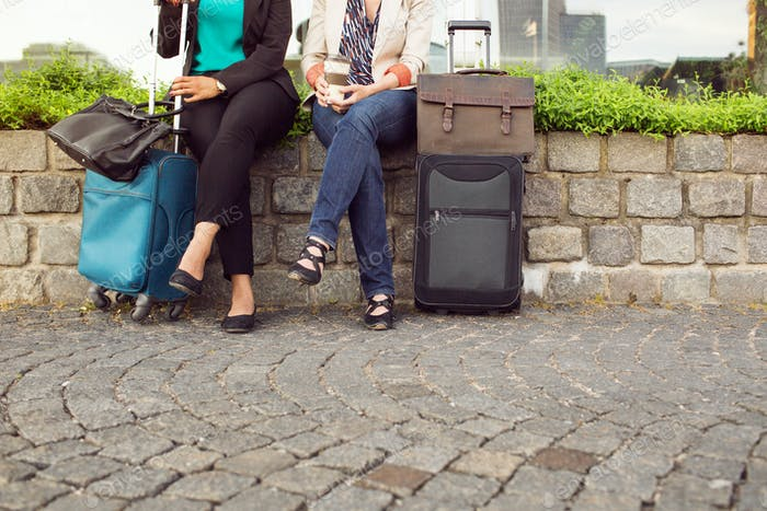 Businesswomen with suitcases sitting
