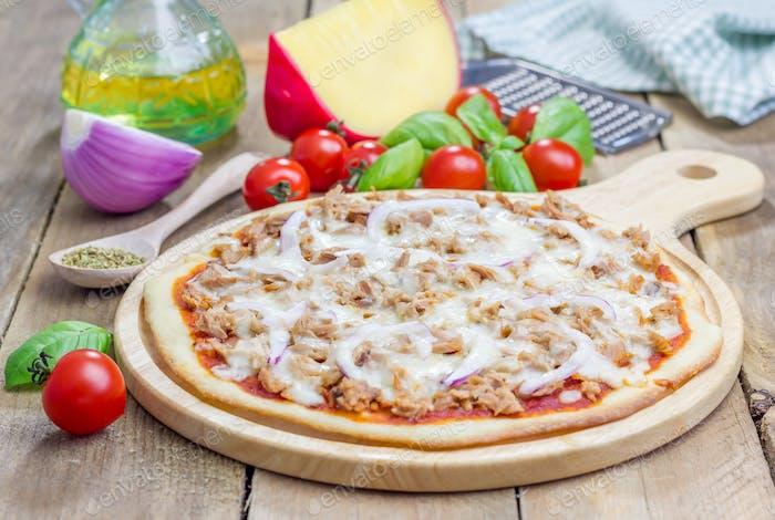 Pizza mit Thunfisch auf einem Holzbrett