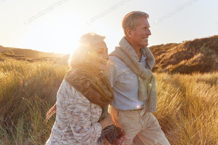 Liebevolle pensionierte Paar Walking Arm In Arm Durch Sand Dünen Am Strand Urlaub Gegen Abfackeln Sonne