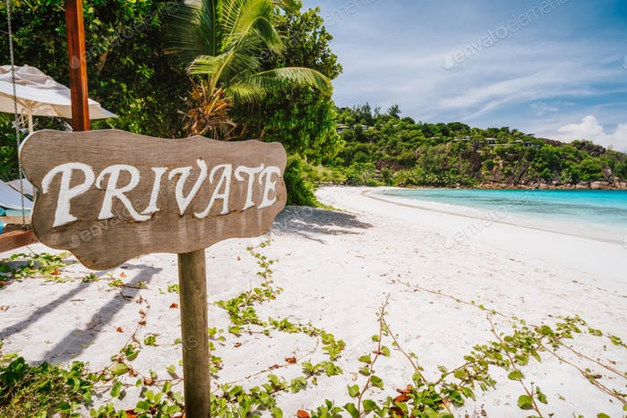 Private sign at tropical sandy beach with blue ocean lagoon in background at Mahe island, Seychelles