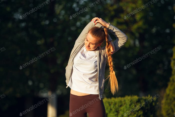 Young female runner, athlete is stretching before jogging in the city street in sunshine. Beautiful