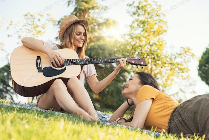Beautiful women having fun playing guitar in the park.