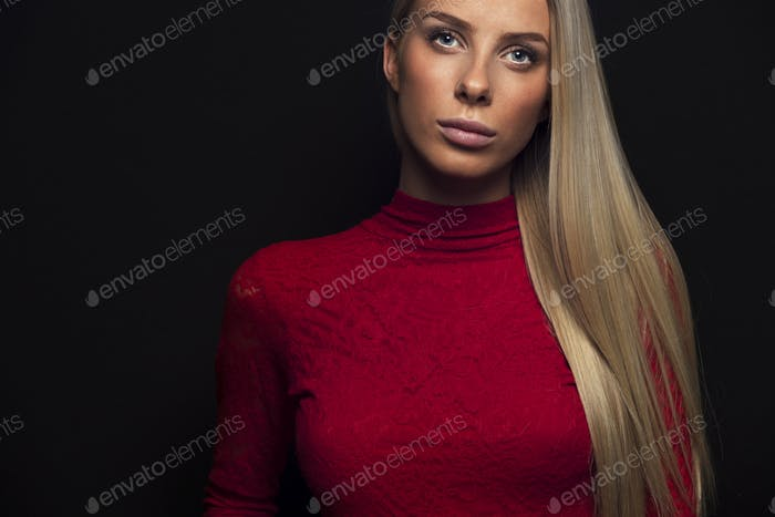 Dark portrait of a blonde woman in red dress
