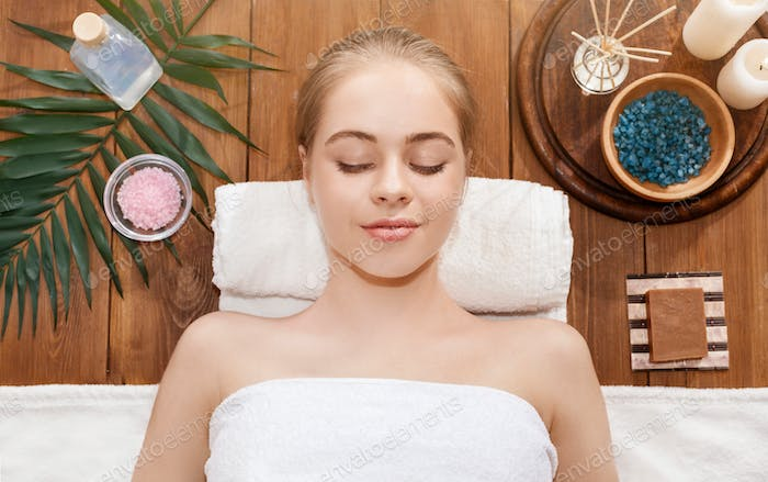 Massage with sea salt. Girl lies on table with spa accessories