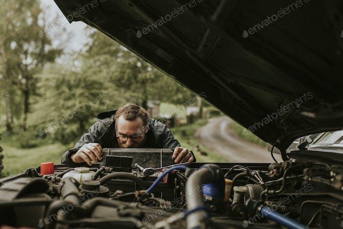 Man repairing a car engine outdoors
