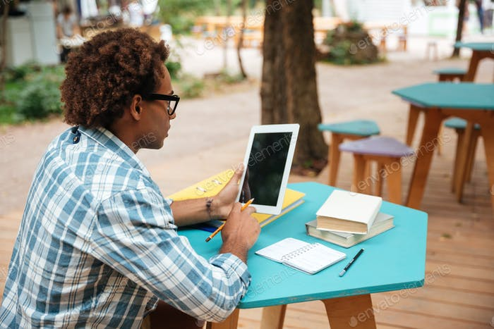 Arfican man using blank screen tablet in outdoor cafe