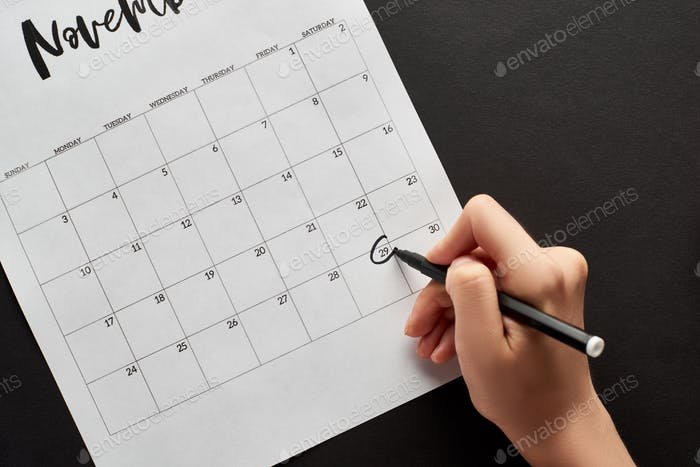 Cropped View of Woman Marking Black Friday Date in Calendar on Black Background