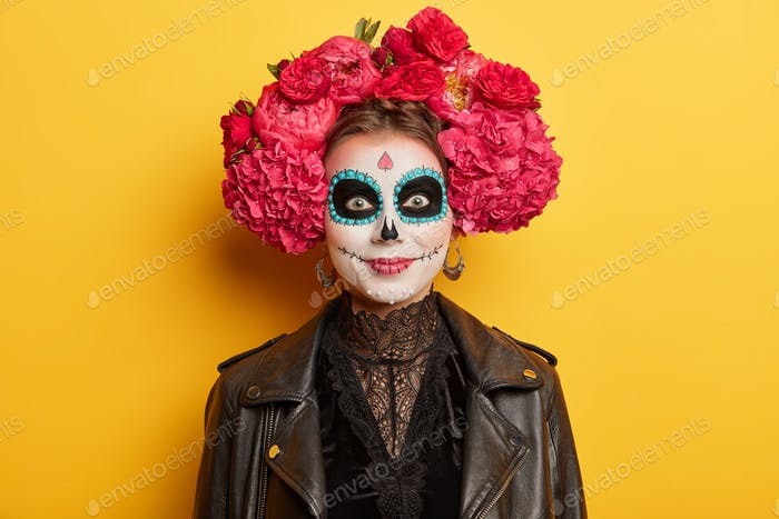 Cheerful female with artistic halloween makeup wears traditional attire for mexican day of death to