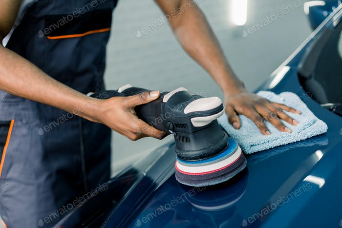 Car detailing and polishing concept. Hands of professional African man worker, with orbital polisher