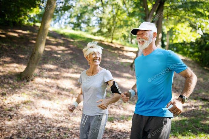 Glückliche ältere Paar bleiben fit durch Sport laufen