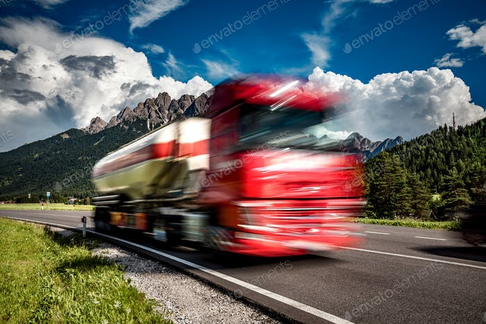 Fuel truck rushes down the highway in the background the Alps. T