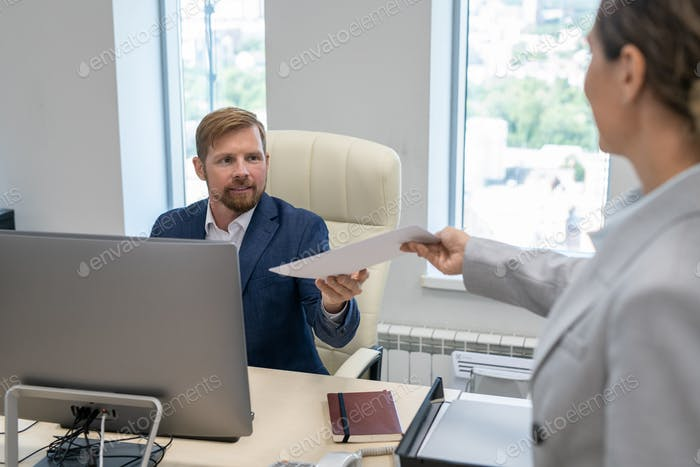 Young businessman taking financial papers given by his colleague