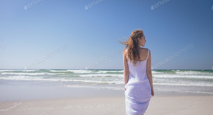 Rear view of beautiful Caucasian woman standing at beach on a sunny day