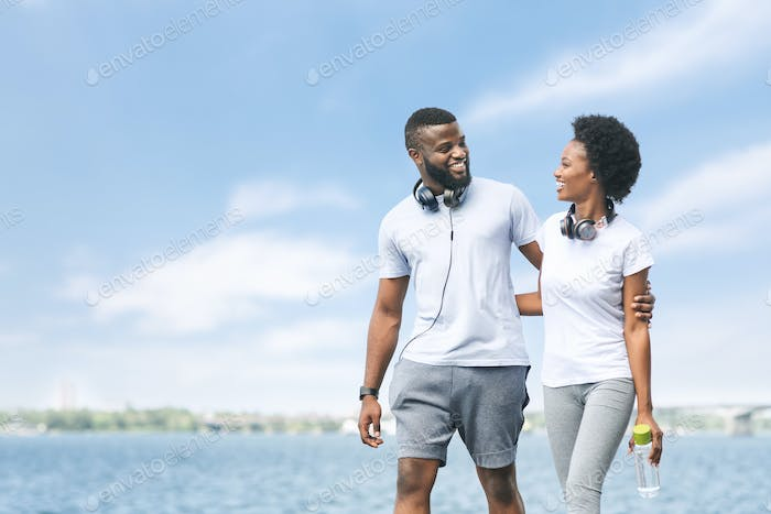Happy Afro Couple Hugging Walking Along River Embankment After Jogging