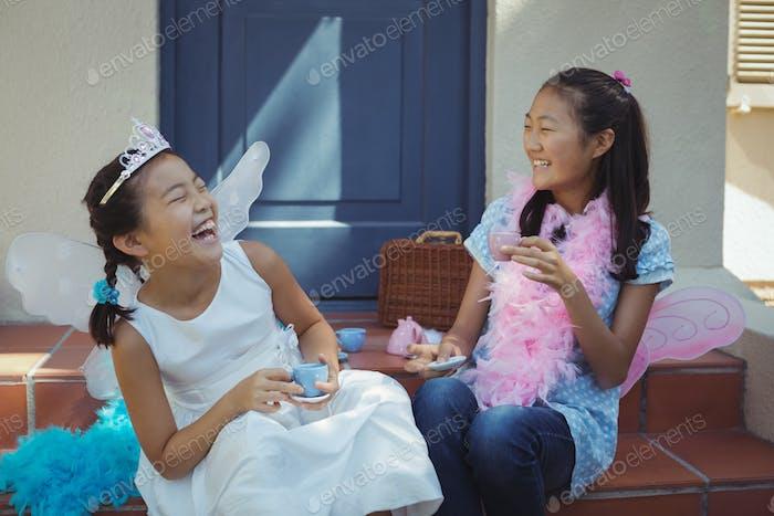 Siblings in fairy costume having a tea party