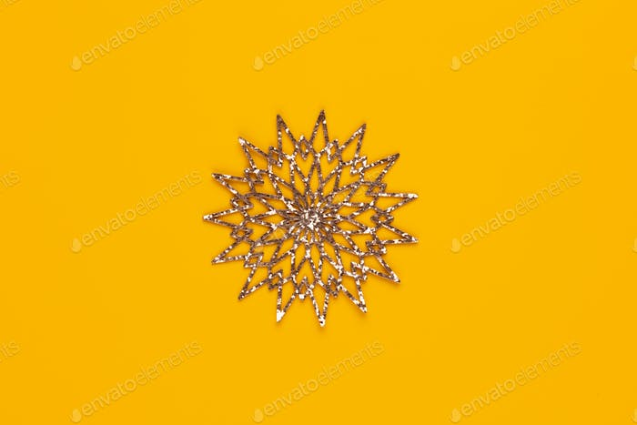 Christmas star decor on yellow colored background.