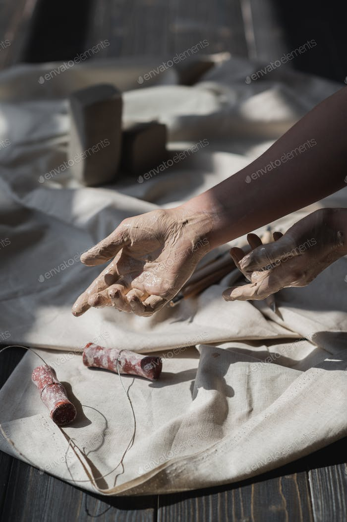 Hands stained in clay going to take cut tool from wooden table, art therapy concept