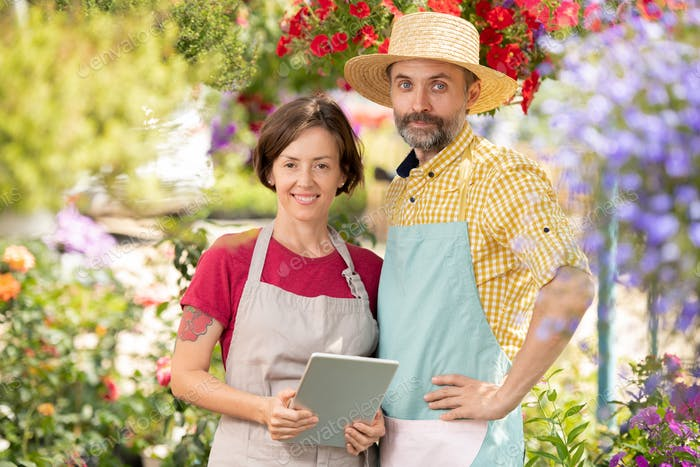 Two successful farmers in workwear standing among blooming flowers