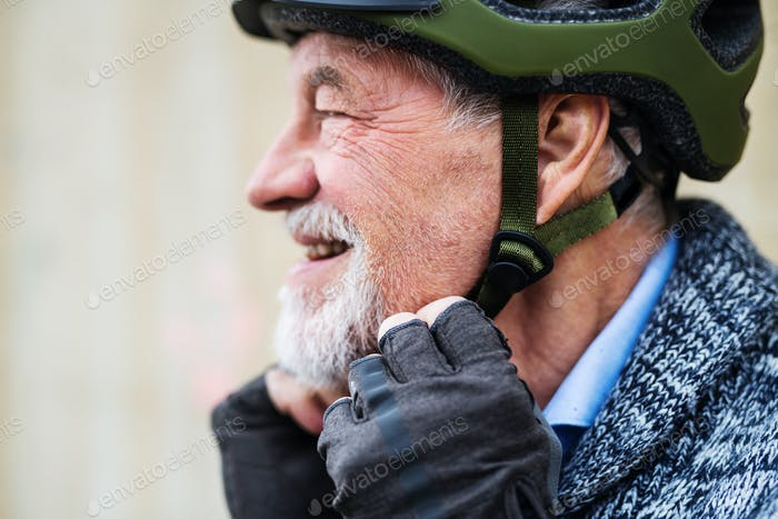A close-up of active senior man standing outdoors, putting on bicycle helmet.