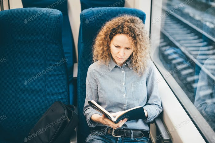 Female passenger of train working remotely in the train.