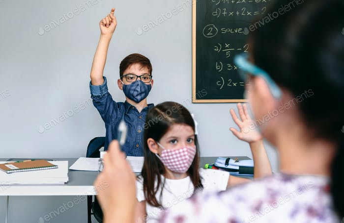 Students with masks raising hands at school