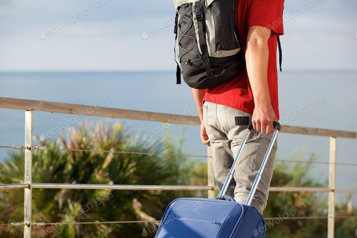 Mann Reisen mit Rucksack und Ziehen Koffer außerhalb