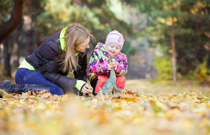 Little girl and mother playing with toy dinosaur outdoors