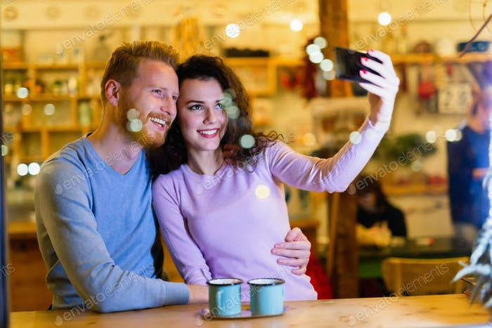Happy couple taking selfie in coffee shop