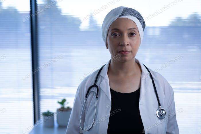 Porträt von gereiften gemischten Rasse Ärztin stehend und Blick auf Kamera in Klinik im Krankenhaus