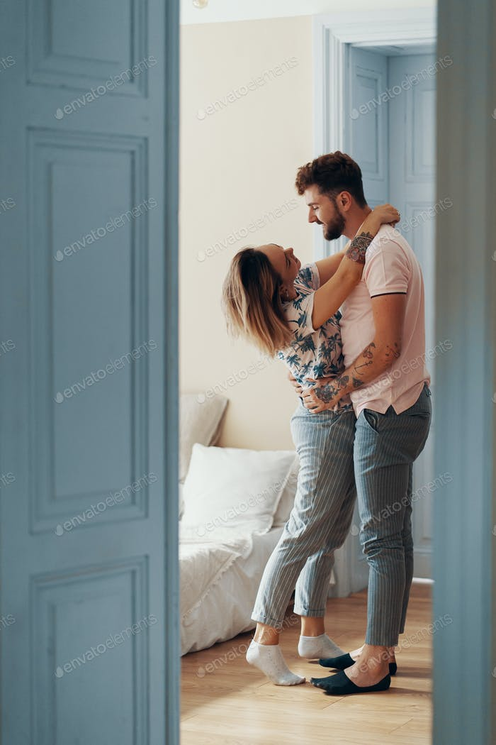 Profile view of loving young couple hugging while standing in their bedroom