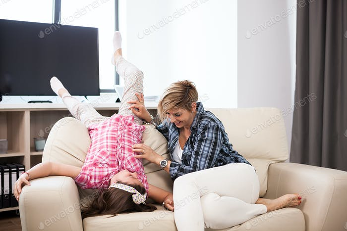 Middle aged woman on the couch with her teenage daughter