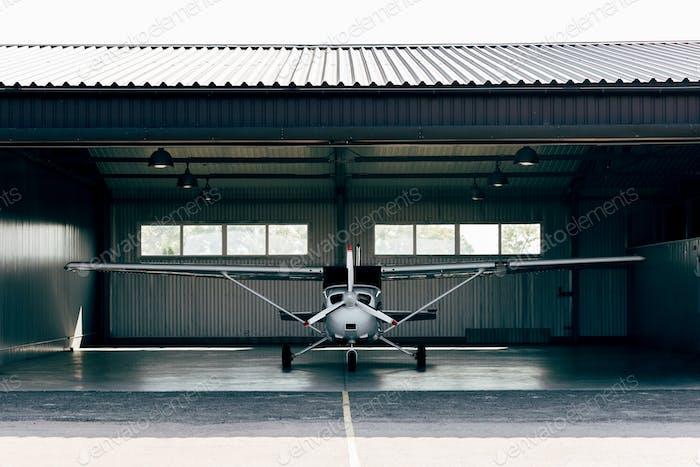 small modern white airplane standing in hangar