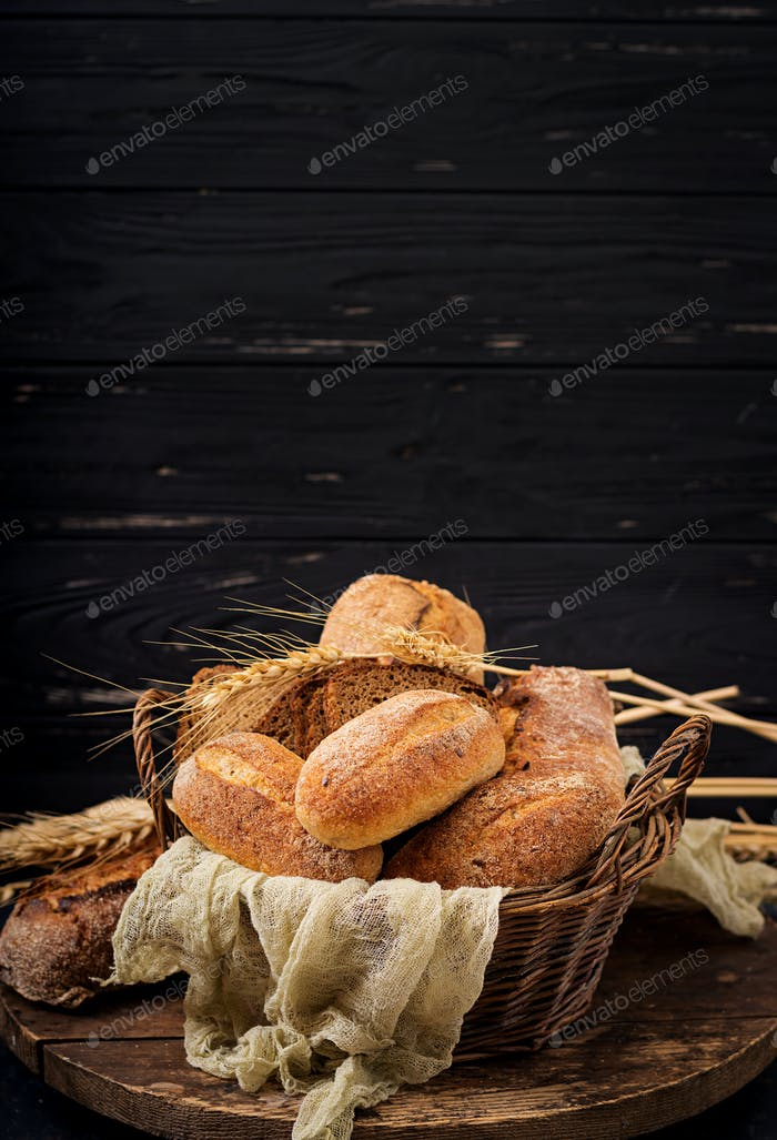 Assortment of baked bread and bun on a wooden background