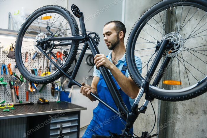 Bicycle repair in workshop, man checks mechanisms