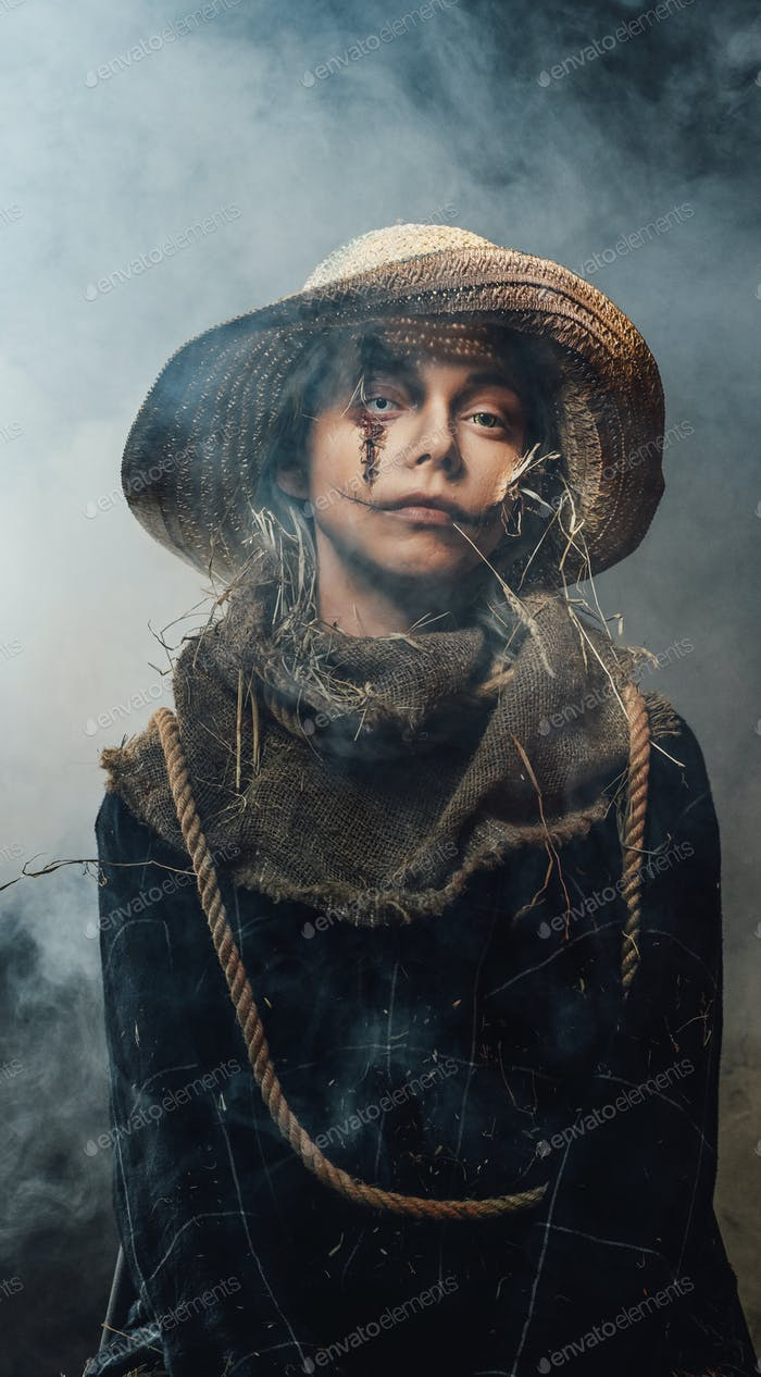 Ragged woman with make up posing with straw hat