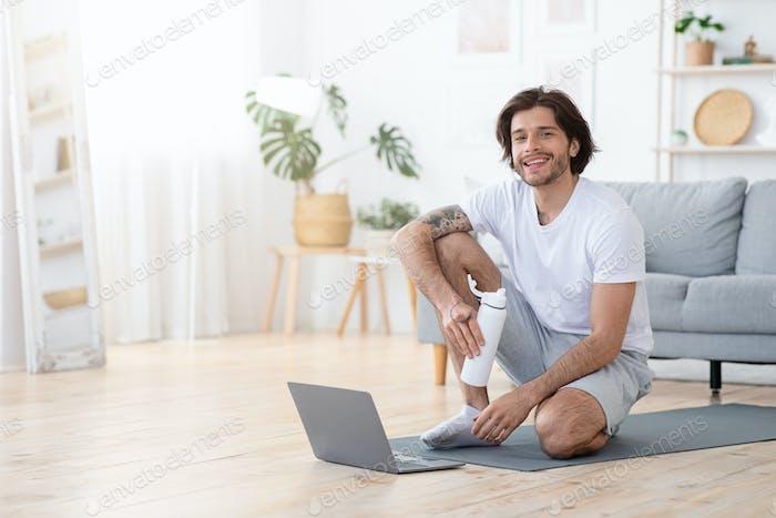 Lächelnder sportlicher Mann Trinkwasser während der Ruhe