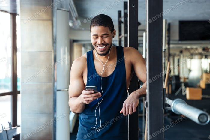 Фитнес-человек с помощью смартфона в тренажерном зале