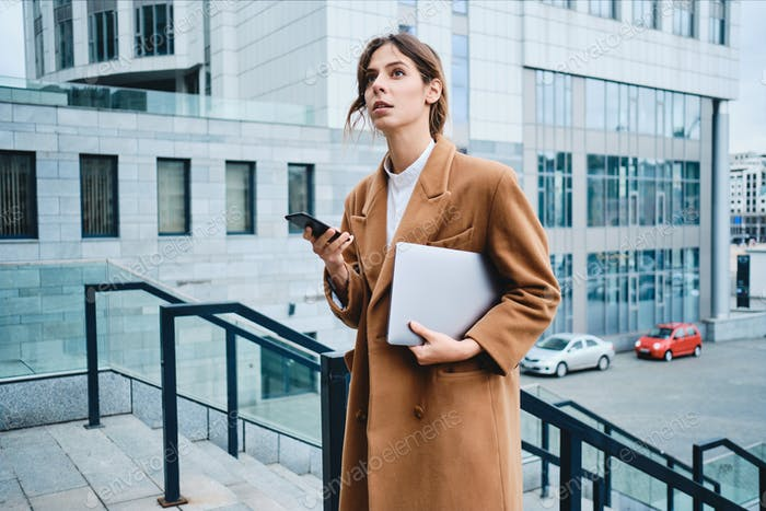 Young lawyer in coat with laptop and cellphone thoughtfully looking away outdoor