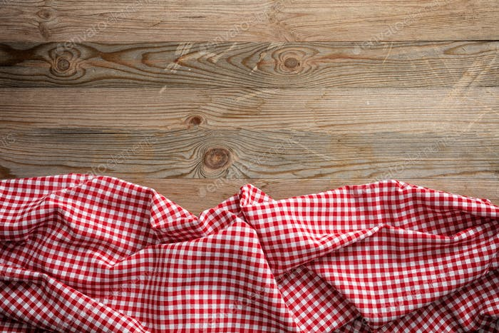Red white checkered picnic tablecloth on wooden background, copy space