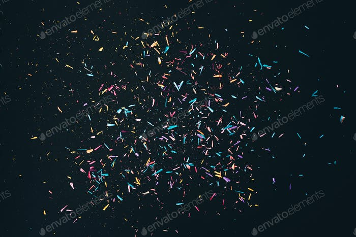 Colorful pencil shavings on black background.