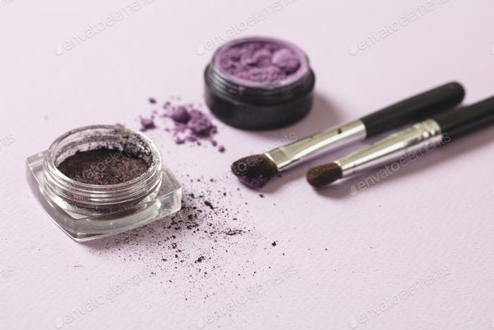Eyeshadow purple color against pink background, copy space