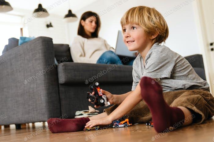 Junge spielt auf dem Boden mit Autospielzeug