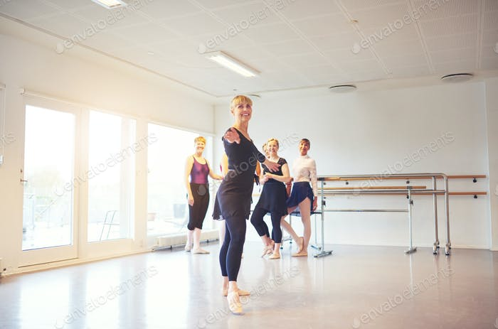 Smiling mature woman doing ballet in a dance studio