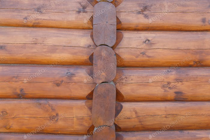 Wall background of round logs house, covered with protective impregnation.