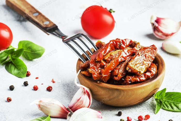 Sun dried tomatoes in olive oil with green basil and spices