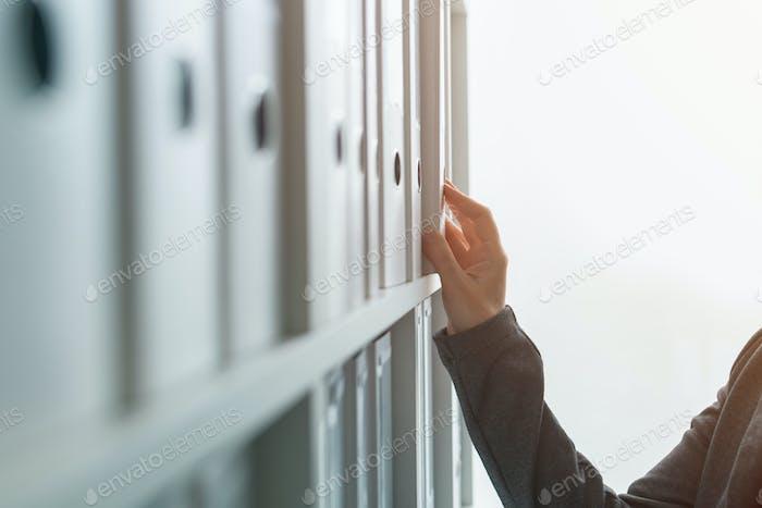 Businesswoman browsing through ring binder file documentation ar