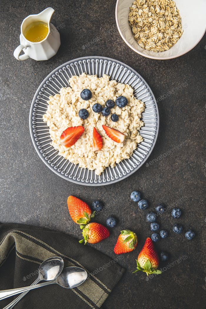 Plate of oatmeal porridge with strawberries and blueberries.