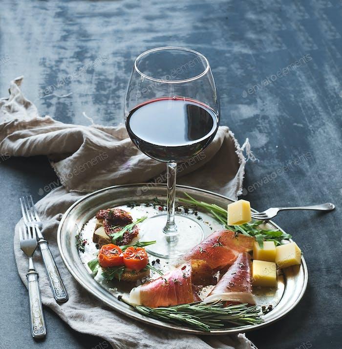 Wine appetizer set. Glass of red wine, vintage dinnerware, brushetta with cherry, dried tomatoes
