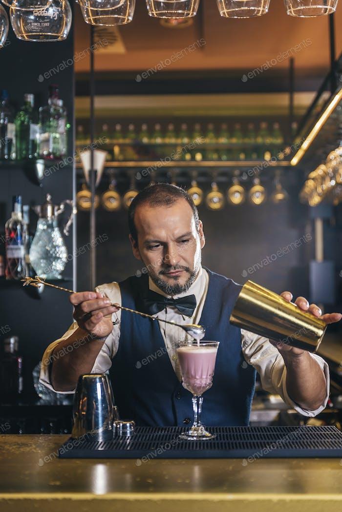 Barman is making cocktail at night club